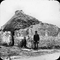 Man And Two Children At A Thatched Cottage