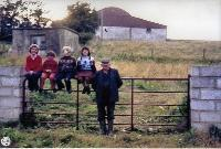 Children Sitting On Gate With Man To The Right In Baile na nGall, Ring.